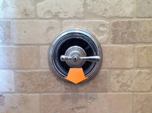 Shower handle with arrow pointing out from wall